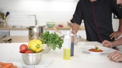 Cook student preparing dish with help of chef Stock Footage