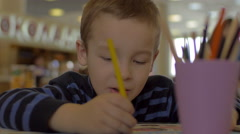 At the table sitting a little boy and draws with colored pencils Stock Footage
