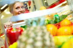 Face of a young woman behind the shopping trolley, looking at camera and smiling Stock Photos