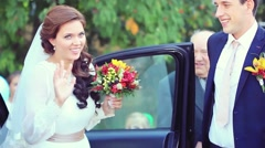 Groom open the door of wedding car and take hand to bride and smiling. 1920x1080 Stock Footage