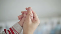 An infant holding an adult's thumb Stock Footage