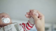 An infant boy with a baby's dummy holding an adult's thumb Stock Footage