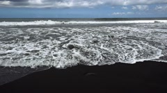 Black volcanic sand beach with water coming up and wave crashing, slow motion Stock Footage