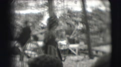 1948: woman carries two birds in cages, people follow carrying large crate Stock Footage