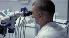 Male dentist receiving the root canals of the patient using the microscope Stock Footage