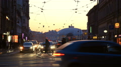 At sunset at intersection people crossing road, passing cars Stock Footage