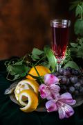 Still life in antique style with a glass of wine, grapes and two lemons Stock Photos