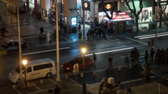 Timelapse of night city with busy intersection with passing cars and pedestrians Arkistovideo