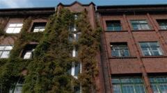 Tilt down. Stylish red brick building in the Badeschiff neighbourhood in Berlin Stock Footage