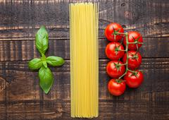 Fresh tomatoes with raw spagetti and basil on gunge background. Set up as ita Stock Photos