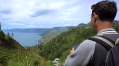 Young man taking photo of Toba Lake, North Sumatra, Indonesia. Stock Footage