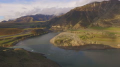 Two rivers merge into the beautiful mountain landscape, aerial view Stock Footage