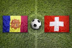 Andorra vs. Switzerland flags on soccer field Stock Photos