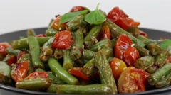 Cooked green beans, red cherry tomato with sesame seeds in black plate, close up Stock Footage