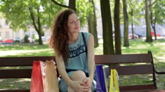 Pretty girl sitting on the bench in the park and looking happy Stock Footage