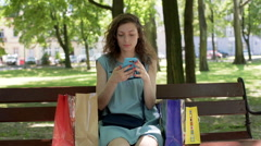 Girl doing photos of shopping on the smartphone in the park Stock Footage