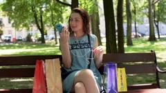 Happy girl talking on loudspeaker on smartphone in the park Stock Footage