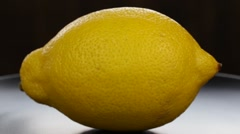 Yellow lemon turning on itself on a black plate background, close up Stock Footage