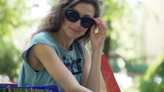 Pretty girl wearing sunglasses and smiling to the camera in the park Stock Footage