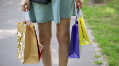 Stylish girl looking thoughtful while standing with her shopping bags in the par Stock Footage