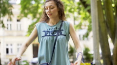 Girl showing shopping bags to the camera and smiling in the park Stock Footage