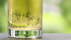 Slow motion 180fps beer bubbles into the glass on stone board with green nature Stock Footage