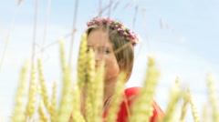 Pretty girl in wreath of flowers looking thoughtful while standing in the grain  Stock Footage