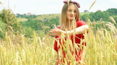Pretty girl wearing wreath of flowers and smiling to the camera in the grain fie Stock Footage
