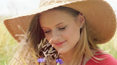 Girl in straw hat holding field flowers and looking thoughtful Stock Footage