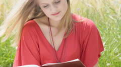 Pretty girl looking absorbed while reading book on the grain field Stock Footage