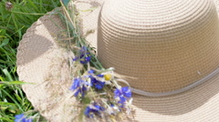 View of female hands putting flowers on the straw hat, steadycam shot Stock Footage