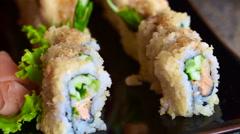 Japanese fusion sushi dish. Tempura maki present on plate Stock Footage
