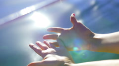 The hands of a beautiful girl on a background of water - sun glare in the water Stock Footage