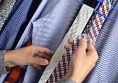 Young man choosing a tie from the closet Stock Photos