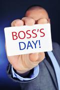 Man with a signboard with the text boss day Stock Photos