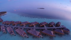 Aerial of sunset over sea luxurious villas on tropical island resort, Maldives. Stock Footage