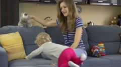 Babysitter woman have fun with baby girl on sofa at work Stock Footage