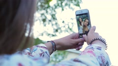 Young women are taking a selfie and making funny faces by smartphone. Arkistovideo