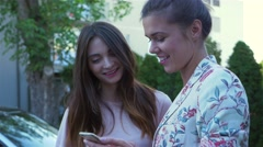 Two young women are talking and using smartphone to show something. Arkistovideo
