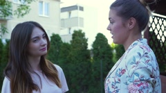 Two young women are talking and describing something to each other Stock Footage