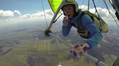 Woman paints her lips with lipstick in flight on a hang-glider Stock Footage
