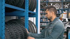 Smiling man auto mechanic carrying new tire in tire store choosing for his car Stock Footage