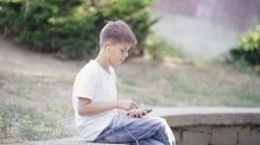 Young teenage boy in headphones with smartphone sitting on the curb listening Stock Footage