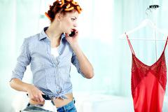 Young woman preparing for her date and talking on the phone Stock Photos