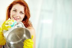 Young beautiful woman washing a saucepan, looking at camera and smiling Stock Photos