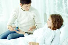 Man giving pills and glass of water to his ill wife Stock Photos