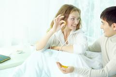 Young smiling woman in bed taking vitamin C offered by her husband Stock Photos