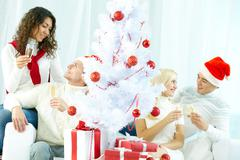 Four loving people congratulating each other at Christmas tree Stock Photos