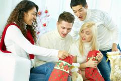Happy girl showing presents to her friends in Christmas stocking Stock Photos