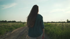Teen girl walking on old road near fields in sunset to camera shot with Stock Footage